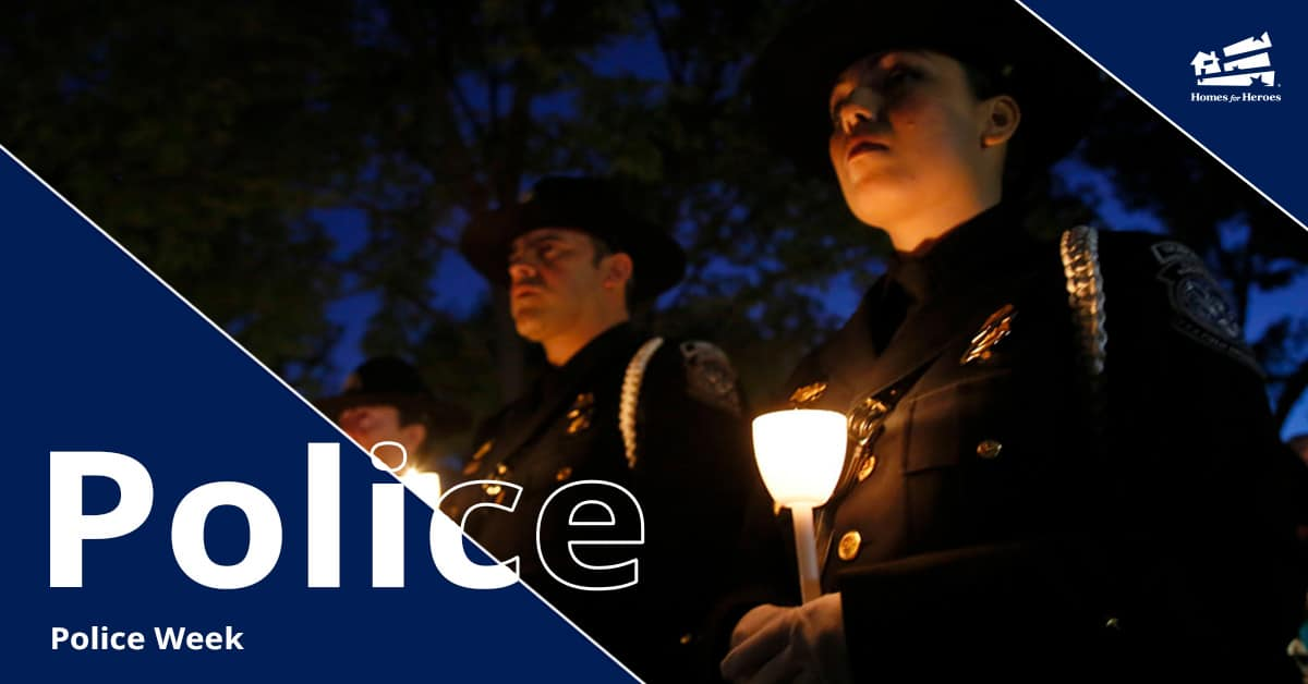 Female and male police officers holding a candle at a vigil for national police week