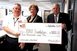 Homes for Heroes Specialist, Benny Persichetti, presents the FDNY Foundation with a $5,000 grant on behalf of the Homes for Heroes Foundation.