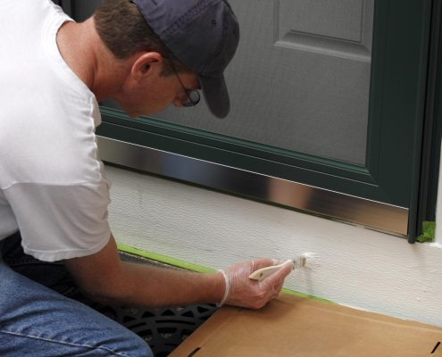 man painting the front door to sell his home faster