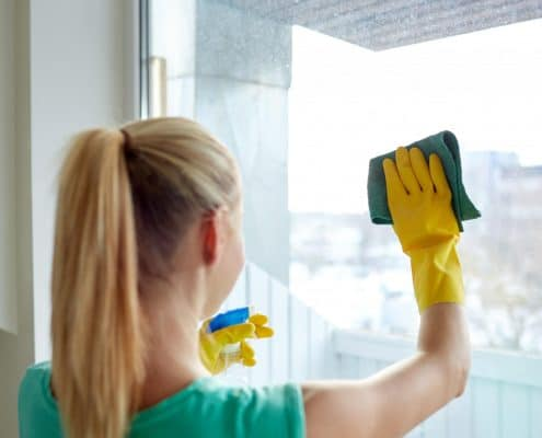 lady cleaning her windows to sell her home