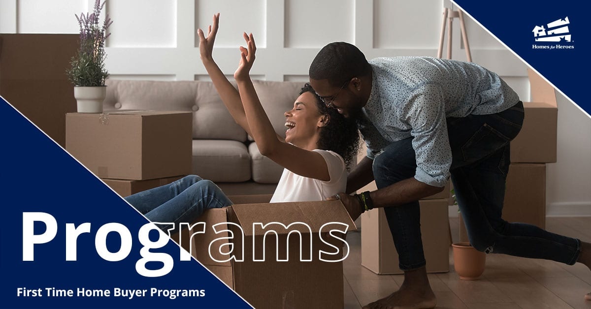 A man pushes a woman in a cardboard moving box across the floor while she laughs and puts her hands in the air
