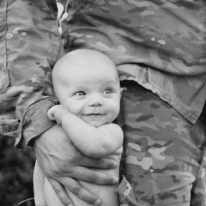 Baby sitting in father's military fatigues