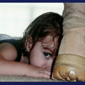 Child hiding behind a boot