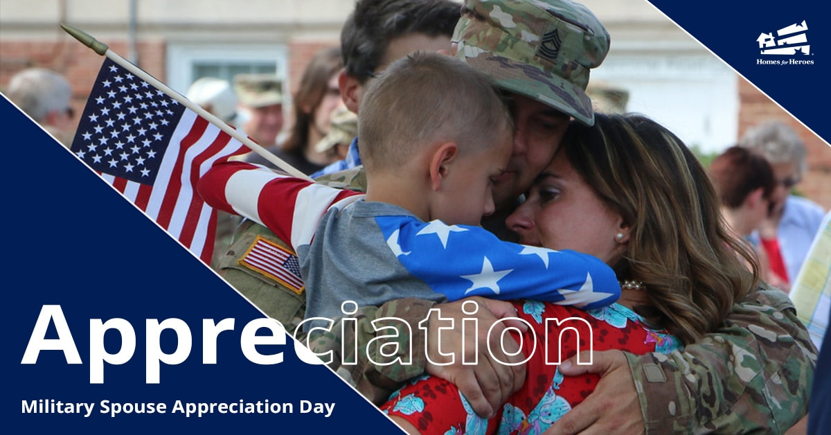 Male Soldier in uniform hugging his wife and young son who is holding an American flag