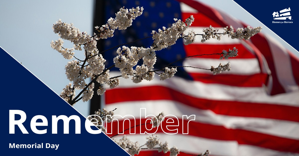 Large United States Flag blowing in the wind in the background with white flowers on a tree in the foreground
