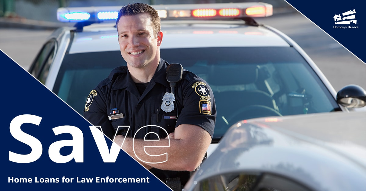 Male police officer leaning on hood of police vehicle with arms crossed smiling in uniform
