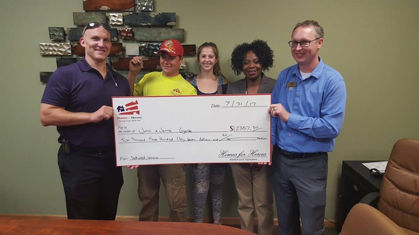 Homes for Heroes affiliates holding big check reflecting Hero Rewards savings received by their hero clients