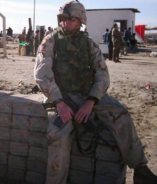 Army Soldier sitting on a wall in Iraq