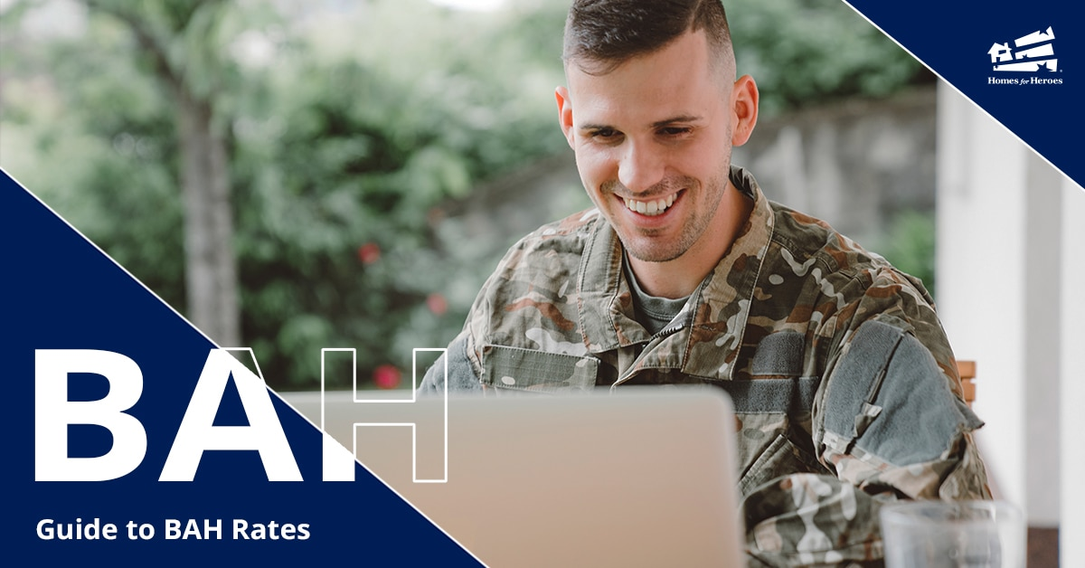 man in military camo smiling while looking at his computer