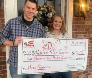 Man and woman hold giant check outside their home