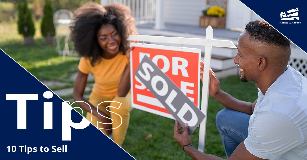 Man and woman in front lawn putting sold sign over their for sale sign