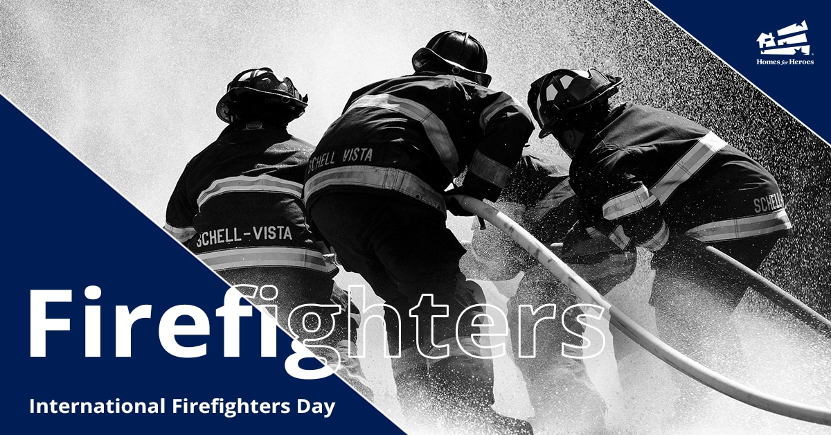 Three firefighters battle a fire with a hose in black and white