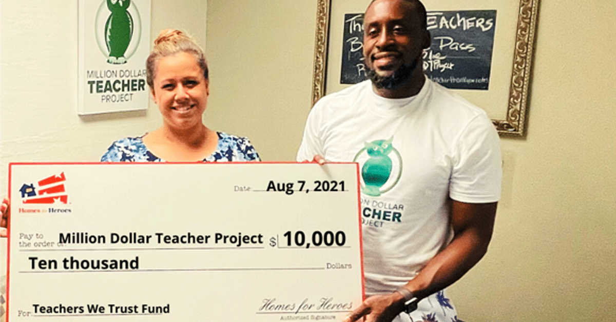Founder of Million Dollar Teacher Project Lloyd Hopkins holds a large check as a donation for $10,000 from the Homes for Heroes Foundation was granted to him