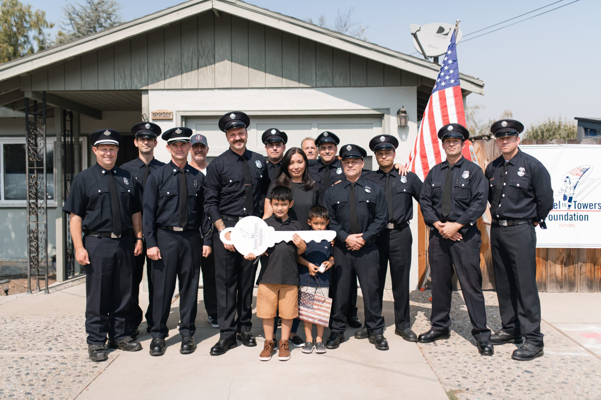 Members of the San Francisco Fire Department stand with Patricia Cortez, Jason Cortez's wife, and their two sons in front of their home.