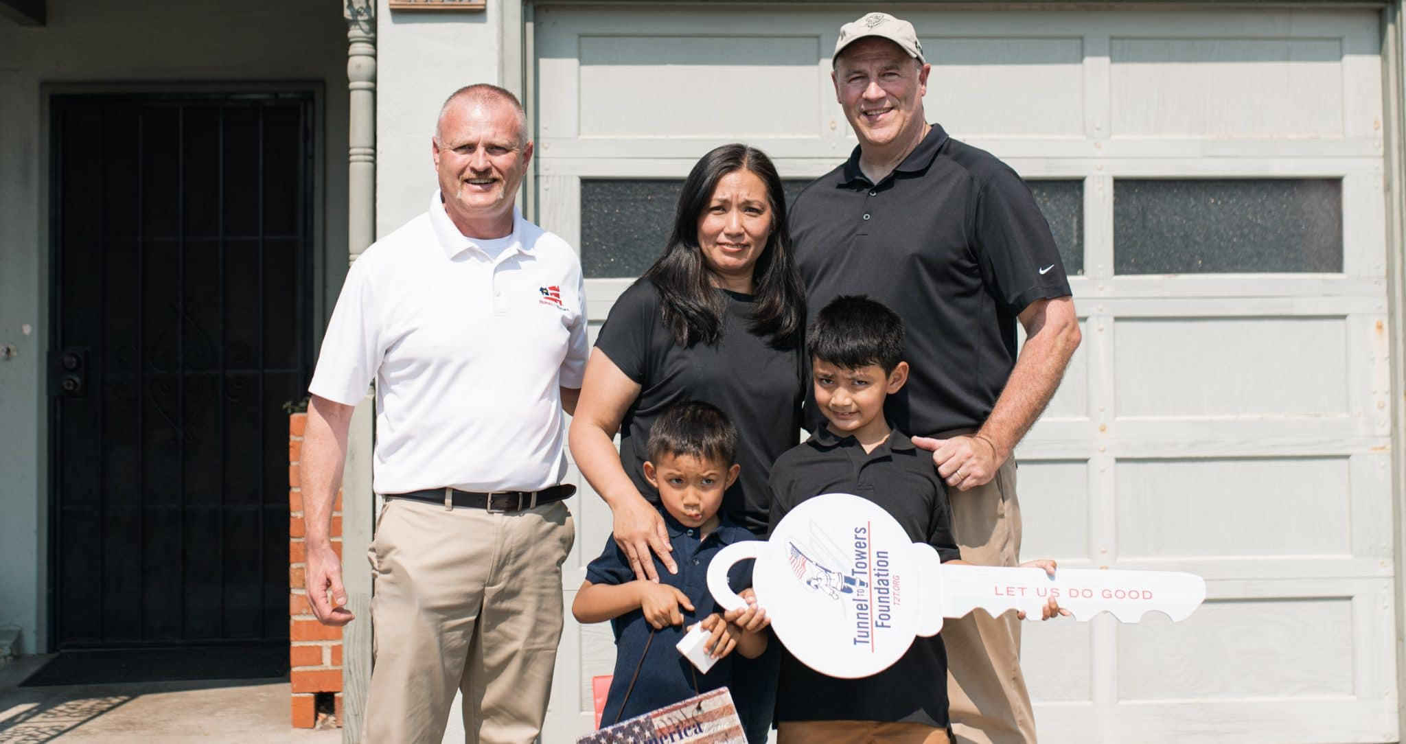 Representatives from Homes for Heroes Foundation and Tunnel to Towers stand with Patricia Cortez and her two sons in front of their San Francisco home