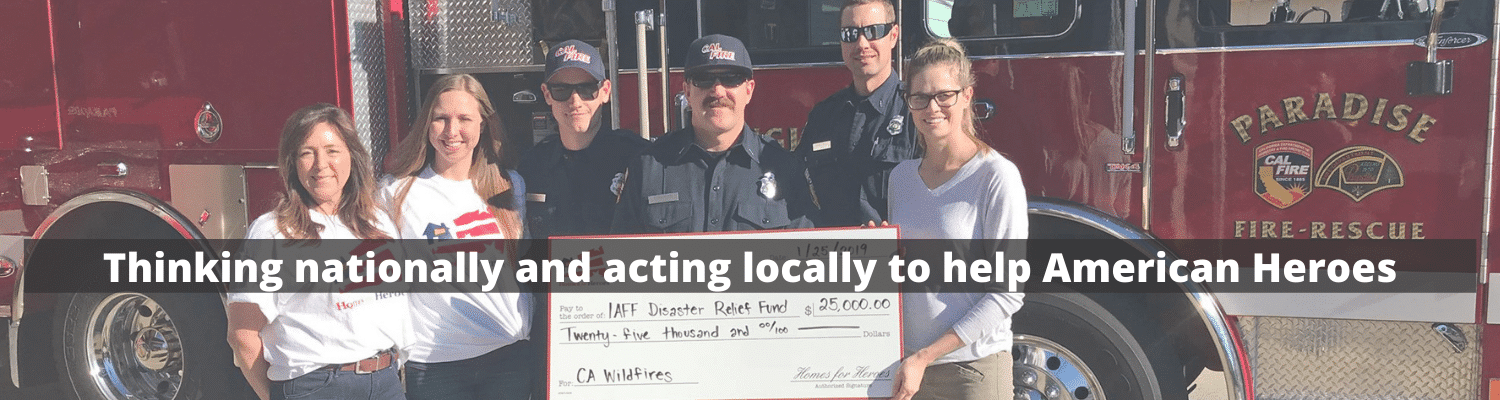 People holding an oversized donation check in front of a firetruck.